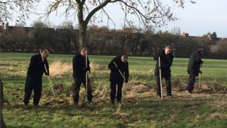 Five men raking leaves on a field