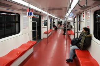 A few passengers sit in an underground train carriage