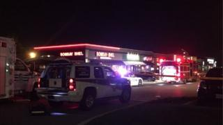 External shot of Indian restaurant at night-time with emergency service vehicles outside