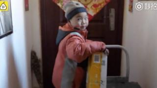 Seven-year-old Chang Jiang holding a parcel