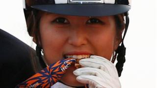 2014年9月20日,郑尤拉在仁川亚运会赢得马术盛装舞步团体金牌,她将金牌咬在嘴里