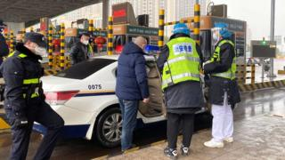 Police inspect a car at a toll station outside Wuhan, China