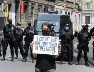 """A protester in front of police in Sarajevo holds a placard that reads: """"It doesn't take that many fascists to make fascism"""". Photo: 16 May 2020"""