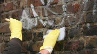 Youths cleaning a wall on a community payback scheme