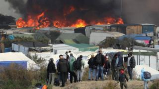 Fire breaks out in the Jungle camp as migrants prepare to leave while the authorities start to demolish the site in Calais, France