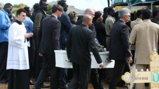 Mourners attend a funeral service for the three children in 2015