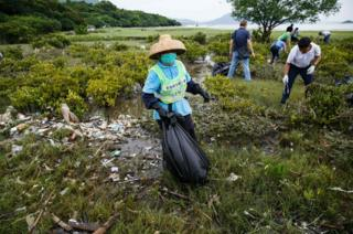 Workers and residents clean up refuse washed ashore at the top of a beach in Hong Kong