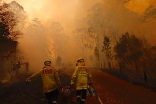 Two firefighters proceed along a road as heavy smoke fills the air, turning the sky a hazy orange