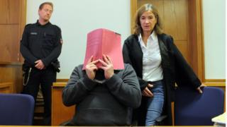 Niels Hoegel hides his face as he appears in court in November 2014