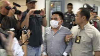 Bach Van Minh, also known as Boonchai Bach (C), a Vietnamese national who also holds Thai citizenship, is escorted by Thai police officers at the Suvarnabhumi airport's police station in Samut Prakan province, on the outskirts of Bangkok, Thailand