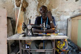 Streetside tailor Ganiyu Oyinlola sits behind a sewing machine for a portrait photograph as he sews near a currency exchange market in Ikeja district in Lagos, Nigeria August 12, 2017.