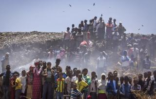 In this Sunday, March 12, 2017 photo, residents look on as rescue efforts take place at the scene of a garbage landslide, on the outskirts of the capital Addis Ababa, in Ethiopia