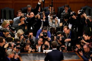 Facebook CEO Mark Zuckerberg is surrounded by members of the media.