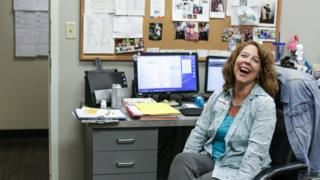 Rhonda Francis at her desk, smiling