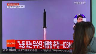 A woman walks past a television screen showing file footage of North Korea's missile launch at a railway station in Seoul