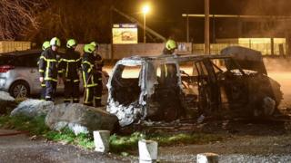 Firefighters extinguish a car set on fire in the street where riots sparked on March 3, 2019 following the death of 2 young people on a scooter as they were chased by the police last night, in Grenoble central-eastern France.