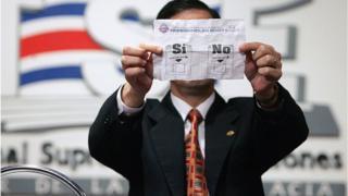 Un funcionario del consejo electoral muetra un boceto de la boleta para el refrendo sobre el TLC con EE.UU. que se celebró en Costa Rica.
