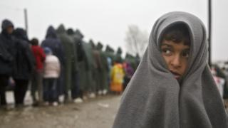 Migrant child covered in blanket stands in rain at Greek border camp near Idomeni, 10 March 2016