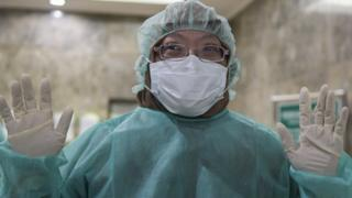 Petugas kementerian kesehatan mengenakan alat pelindung dan masker sebelum masuk ke laboratorium pengujian virus Corona.