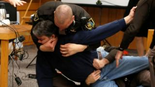 An angry father had to be restrained in court after lunging at paedophile doctor Larry Nassar