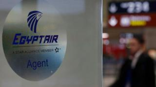 A man passes the Egyptair desk at Charles de Gaulle airport, after an Egyptair flight disappeared from radar during its flight from Paris to Cairo, in Paris, France, May 19, 2016. REUTERS/Christian Hartmann