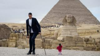 India's Jyoti Amge (R), the world's shortest woman poses for a picture with Sultan Kosen of Turkey, the world's tallest man, at the site of the Pyramids of Giza in Egypt on January 26, 2018, with the Sphinx and the Pyramid of Khafre (also known as Chephren) seen in the background