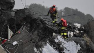 Rescuers climb on foot over large pieces of road wreckage, amid rain and poor conditions