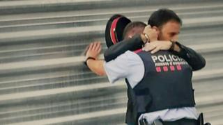 This photograph of a man hugging an apparently distressed Catalan policeman captured an emotional moment for a nation in crisis - what's the story behind it?
