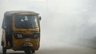 A rickshaw carries passengers through smoke emitted from a dump in the city of Port Harcourt