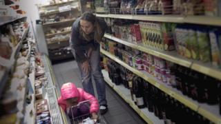 Mujer mirando productos en una góndola del supermercado.