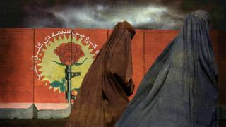 Women walk infront of a blast wall wearing a traditional burka
