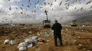 A man stands in front of vehicles arranging piles of garbage at Liosia landfill northeast of Athens