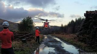 Rescue workers standing near a helicopter