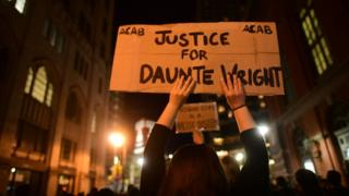 A woman holds up a protest sign for Daunte Wright on April 13, 2021 in Philadelphia, Pennsylvania.