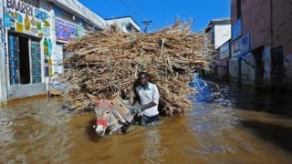 A man walks his donkey and its load through flooded streets Beledweyne, north of Mogadishu