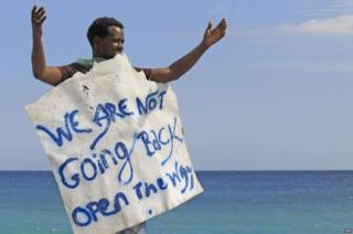"""A migrant holds a placard reading """"We are not going back"""" as he waits near the sea, in the city of Ventimiglia at the French-Italian border, on 15 June 2015"""