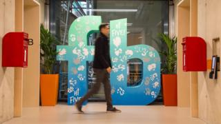 A man walks past a Facebook logo at Facebook's new Frank Gehry-designed headquarters at Rathbone Place in London.