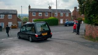 Hearse carries coffin as people watch