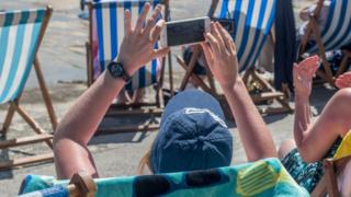 Person using mobile phone on beach