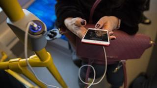 Дівчина заряджає мобільний телефон в салоні трамвая у Києві, 12 січня 2018 р.