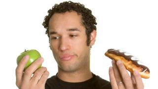 Hombre con una manzana y un dulce.