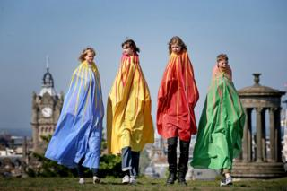 "Dressed in giant capes, children take part in ""The Tallest"" one of over 100 pop-up performances featured in this year's Edinburgh International Children's Festival"