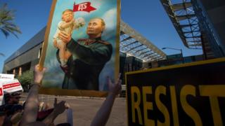 плакат - путин держит трампа на руках