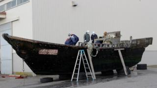 Coast guard officials investigating a wooden boat at the Fukui port in Sakai city in Fukui prefecture, western Japan