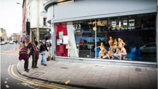 People posed in a window in Bristol