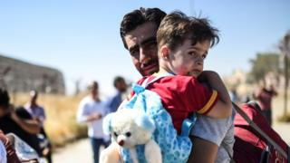 Syrian refugees are pictured on their way back to the Syrian city of Jerabulus