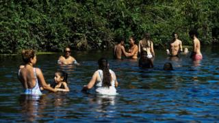 People enjoy the hot weather in the River Lea in east London