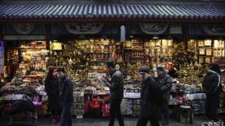 Chinese shoppers walk through a market