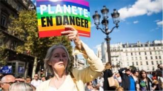 """Учасниця демонстрації тримає банер """"Планета в небезпеці"""" на акції протесту у Франції"""