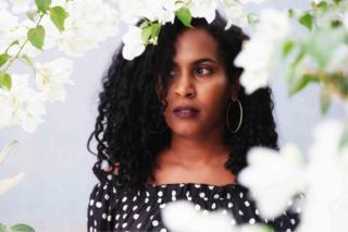صورة امرأة ذات شعر مموج تحيط به الزهور